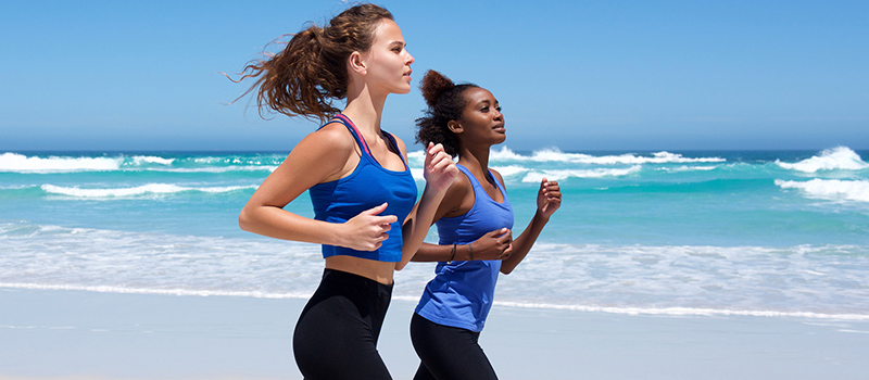 Side portrait of two young women running along the beach